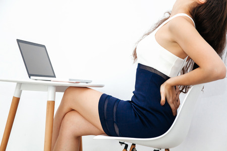 working stiff: Young woman having chronic back pain  backache  office syndrome while working with laptop on white desk over white isolated background