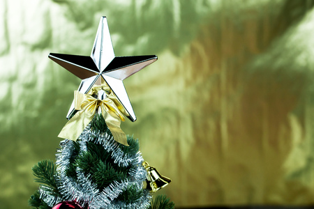 tinsel: Top of Christmas tree decorated with star in bright golden shiny background.
