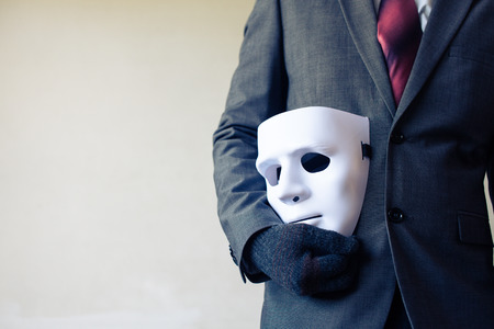 fraudster: Business man carrying white mask to his body indicating Business fraud and faking business partnership