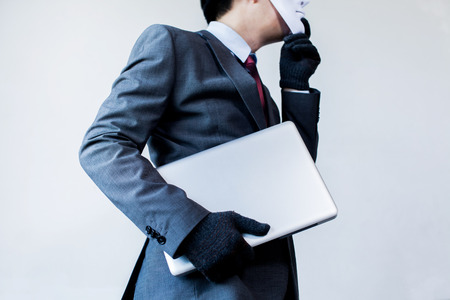 Business man in white mask wearing gloves and stealing computer and digital information - fraud, hacker, theft, cyber crime concept