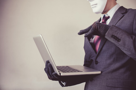 Business man in white mask wearing gloves and using computer - fraud, hacker, theft, cyber crime concept