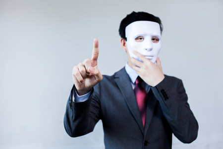 Anonymous businessman in mask hiding himself touching on virtual screen - with copyspace.
