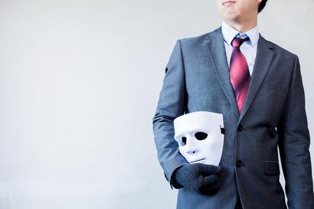 사업 사기와 가짜 사업 제휴를 나타내는 그의 시체에 흰색 마스크를 들고 비즈니스 남자