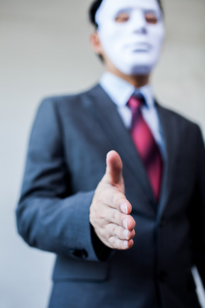 Business man giving dishonest handshake hiding in the mask - Business fraud and hypocrite agreement. Reklamní fotografie - 66136399
