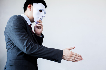 fraudster: Business man giving dishonest handshake hiding in the mask - Business fraud and hypocrite agreement.