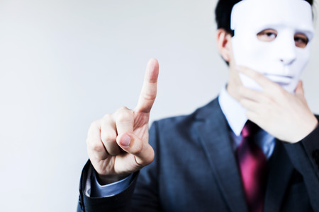 fraudster: Anonymous businessman in mask hiding himself touching on virtual screen - with copyspace.