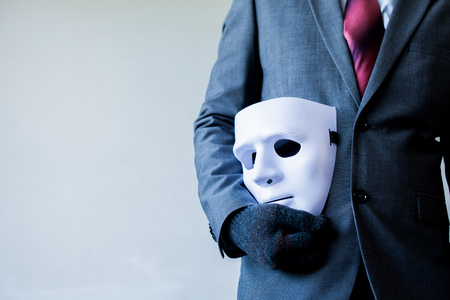 betray: Business man carrying white mask to his body indicating Business fraud and faking business partnership.