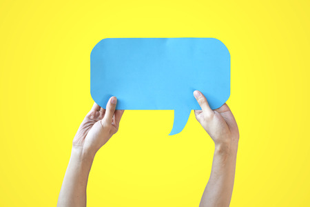 Human Hands Holding Blue Speech Bubble Over Yellow Background - Balloon speech bubble concept Stock Photo
