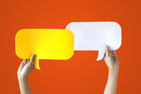 Human Hands Holding Yellow and White Speech Bubbles Over Orange Background - Balloon speech bubble concept