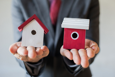 decide: Businessman holding two houses and can not decide choosing the right house.