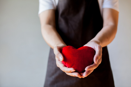 service: Servicing man in apron holding heart - customer relationship and service minded business concept. Stock Photo