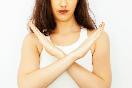 Closeup of Beautiful young Caucasian woman in smart casual dress say no with crossed arms hands Stock Photo