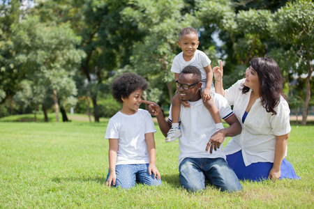 good times: African American family alongside with Asian mum being playful and having good times in the park.