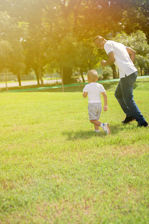 Father and son running and chasing each other in green park.