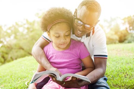 Afro-Amerikaanse familie het lezen van een boek samen in de openlucht park