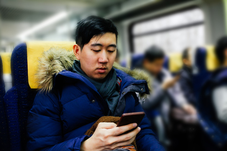 Asian man using smartphone on the public train in winter