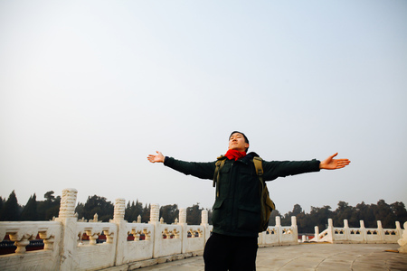 arms wide open: Asian man stretching arms wide open in Chinese architecture Stock Photo
