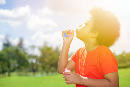African American child  blowing bubbles in the park in summer Stock Photo