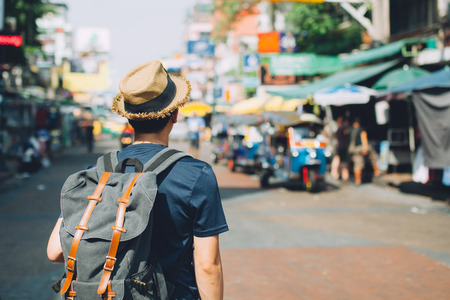 Young Asian traveling backpacker in Khaosan Road outdoor market in Bangkok, Thailand