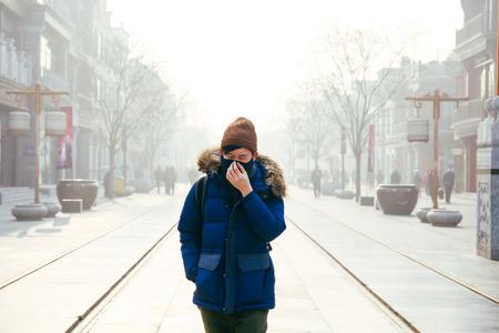 베이징, 중국에서 심각한 대기 오염으로 고통스럽고 안개가 자욱한 스모그와 헷갈리는 하루에 얼굴 마스크를 쓰고 걷는 아시아 남자 스톡 콘텐츠