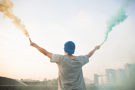 Male teenager holding colorful smoke sticks up in the air over urban city background Stock Photo