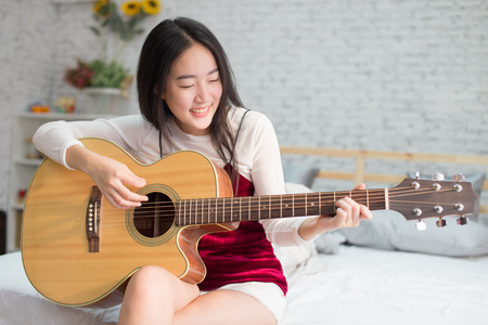 Cute and happy smiling Asian girl playing acoustic guitar in bedroom