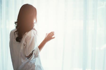 Mujer, tenencia, vidrio, agua, mientras, Mirar, afuera, ventana, espalda, silueta, mujer Foto de archivo - 72661698