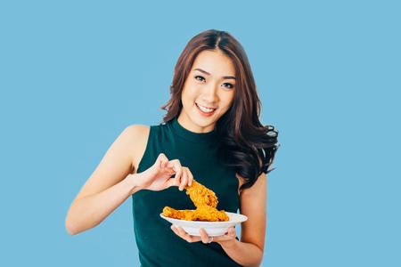 魅力的なアジア女性はれんが造りの白い背景の上にフライド チキンのドラムスティックを食べる