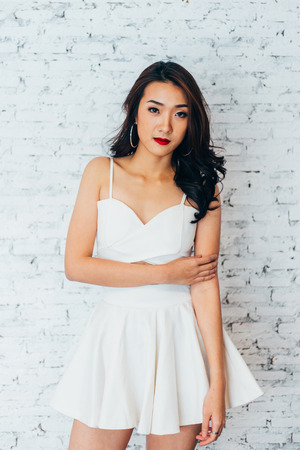 Young Asian woman posing in fashionable dress over white brick wall