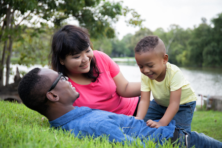 African American family and little kid relaxing and playing on green park with copy space