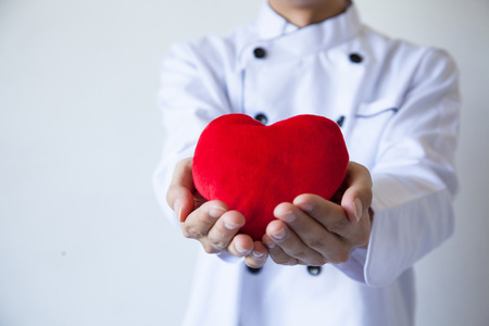 Happy chef holding heart shape with love and passion Stock Photo
