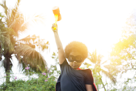 Super hero kid raising hands up with hammer during sunset in the park