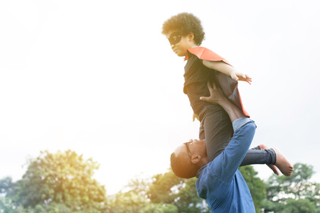 Father holding and helping flying super hero kid togehter in happiness Archivio Fotografico