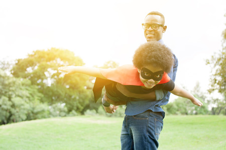Father holding and helping flying super hero kid togehter in happiness Reklamní fotografie