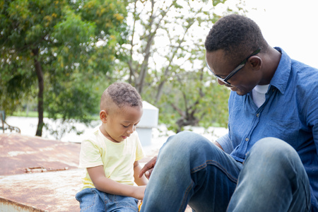 Happy African American father and son enjoying joyful moment together in the outdoor park Stock Photo