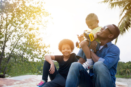 Happy African American father, son and daughter enjoying joyful moment together in the outdoor park
