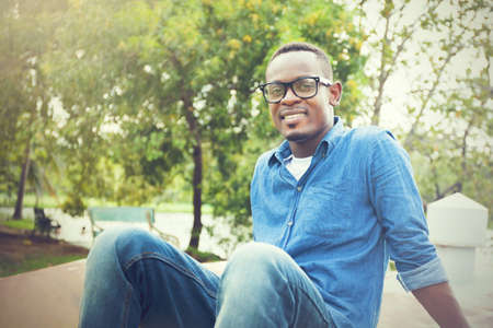 Happy African American man sitting and smiling in the park Stock Photo