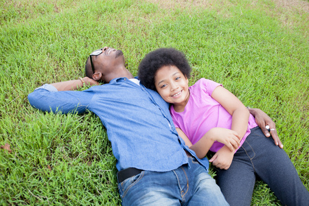 African American Young man and little kid relaxing and looking at clouds on green park Stock Photo