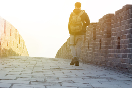 Man walking up and hiking on Great Wall of China during sun set Stock Photo