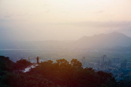 silhouette of man spreading arms out with city and mountain in the background in sunset with big copy space Banco de Imagens