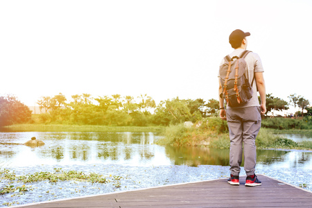 Male travel wanderlust wearing a cap standing at the edge of lake looking away - casual trekking concept