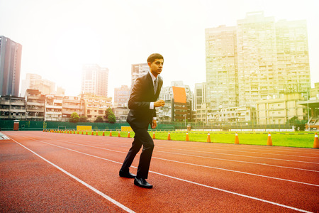 Male determined businessman running on performance race track - challenge and competition concept