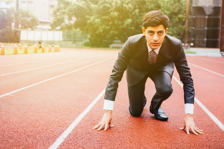 Business man in suit starting and preparing to run on the competition running performance track