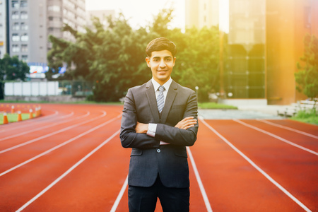 Smiling happy and confident business executive standing with arms folded in performance race track background