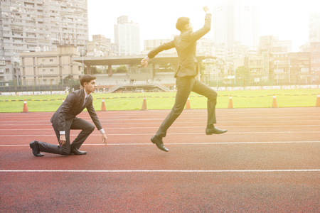 Business man starting new business and work career and winning with success on running track - successful business concept