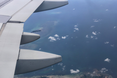 Sky view from above the island through airplane window - travel and vacation concept (selective focus)