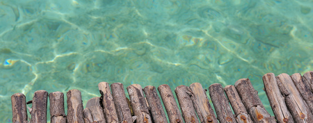 Wood dock pier on beautiful ocean sea water in scene background - used in summer and tourism banner