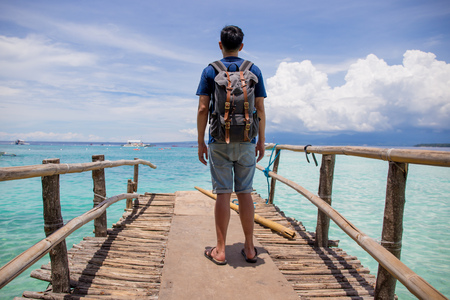 Traveling man with backpack looking out towards the beautiful and crystal clear ocean sea in summer Lizenzfreie Bilder
