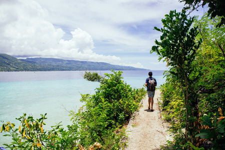Back of backpacker walking and hiking on mountains and sea in tropical summer - with copyspace