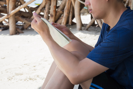 Close-up of relaxing and happy man reading book on the beach Stock Photo